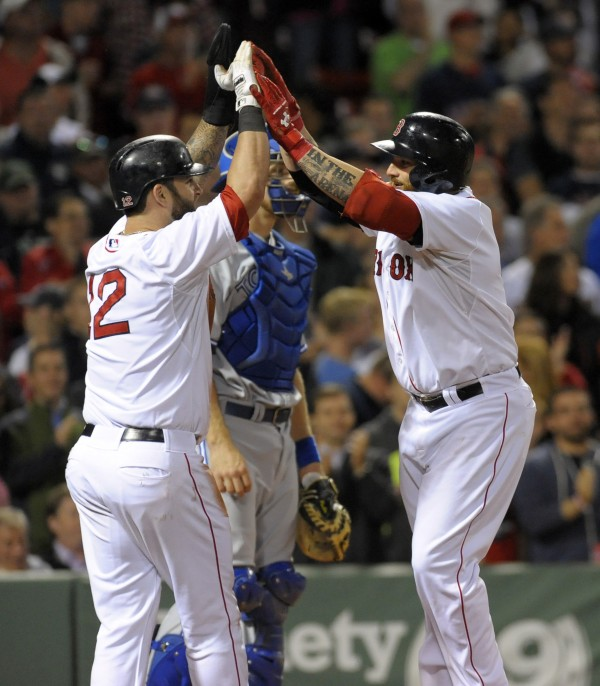 Boston Red Sox first baseman Mike Napoli (left) congratulates teammate Jonny Gomes (5) after Gomes hit a two-run home run during the sixth inning of Tuesday night's game against the Toronto Blue Jays at Fenway Park in Boston.