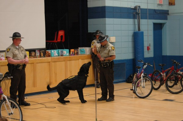Deputy Ryan Allen of the Penobscot County Sheriff's Office demonstrates police dog Dozer's ability to count to students at the Weatherbee school in Hampden.