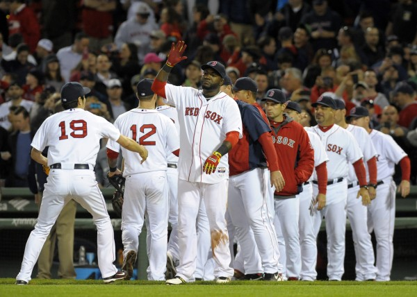 Boston Red Sox designated hitter David Ortiz (34) high fives relief pitcher Koji Uehara (19) after defeating the Cincinnati Reds at Fenway Park in Boston Wednesday night.