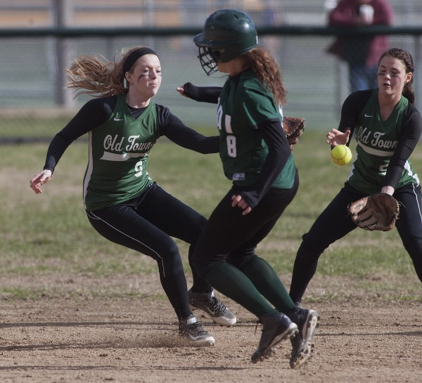 The ball gets between Old Town's Mikayla Richards (9) and Kayla Madden (5), allowing Mount Desert Island runner Ali Bierman (8) to get to second base in the third inning  of their game in Old Town on Monday.