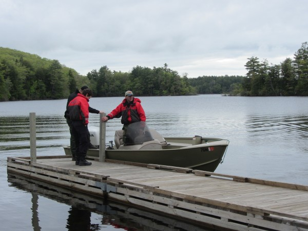 Members of the Maine Warden Service gather at the public boat access lot at Megunticook Lake in Camden as they prepare to send divers into the water in search of a James Wescott, who fell in on Tuesday morning.