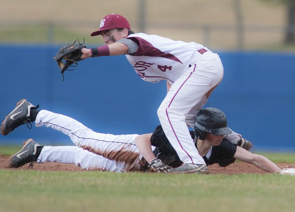 Brunswick base runner Elias Henze dives back under Bangor infielder Kyle Stevenson (4) to avoid the pickoff in the fourth inning of their game at Mansfield Stadium in Bangor on Friday.