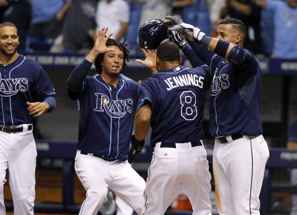 Tampa Bay Rays' Desmond Jennings (8) is congratulated by Yunel Escobar (11) and Juan Carlos Oviedo (46) at home plate after he scored the game-winning run during the ninth inning against the Boston Red Sox at Tropicana Field in Tampa Friday night. Tampa Bay defeated Boston 1-0.