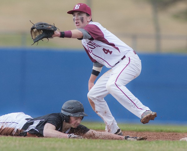 Brunswick base runner Elias Henze dives back to second base under Bangor infielder Kyle Stevenson in the fourth inning of their game at Mansfield Stadium in Bangor on Friday.