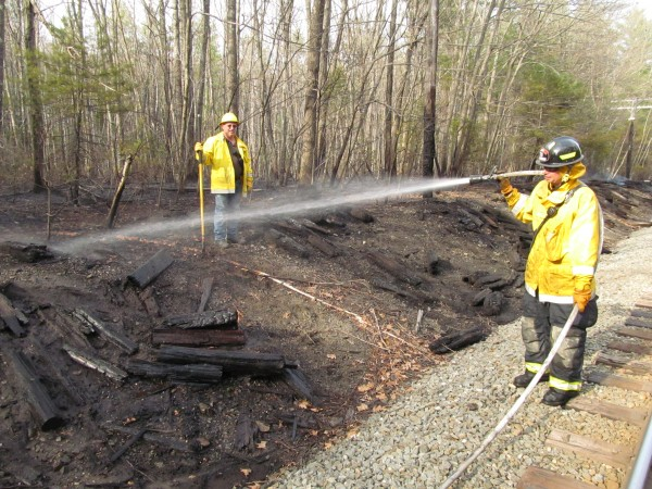 A firefighter sprays water at a lingering hot spot along the railroad tracks in Old Orchard Beach on Thursday evening.
