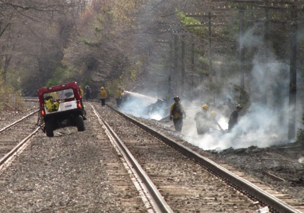 Firefighters working along miles of railroad tracks in Old Orchard Beach attempt to put out the smoking vestiges of a string of brush fires authorities believe were caused by a freight train spraying sparks Thursday afternoon.