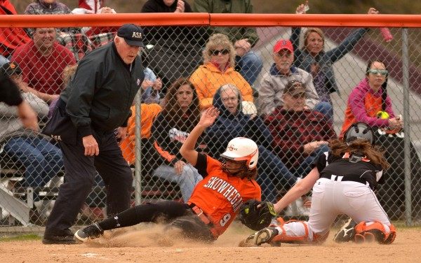 Skowhegan's Taylor Johnson (center) is tagged out at home by Brewer's Sam Pellegrino (right) Friday in Skowhegan. Making the call was umpire Dick Dwyer.