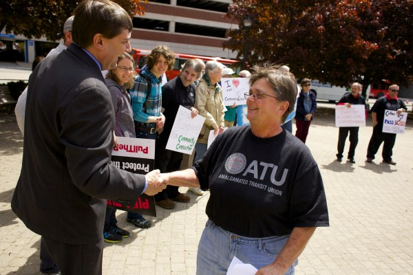 Democratic candidate for congress and state senator Troy Jackson shakes hands with Susan Warner during a demonstration at Pickering Square in Bangor to promote bus usage and support federal public transit funding.