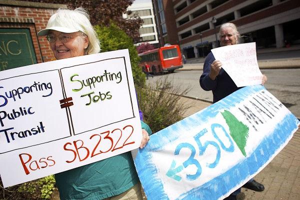 Heidi Brugger of Freedom, left, and Bob Shaw of Belfast hold signs during a demonstration at Pickering Square to promote bus usage and  and federal public transit funding.