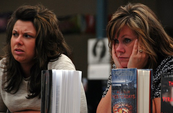Granite Street School teachers Jenny Daigle (left) and Missy Wheaton listen to Millinocket School Committee members discuss closing their school during a meeting at Stearns High School on Wednesday.