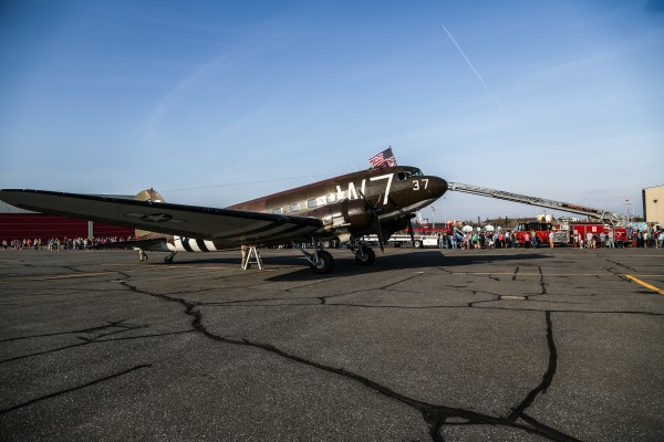 A crowd gathers Friday to see the Whiskey 7, a World War II plane, make its stop in Presque Isle before continuing its journey to Normandy, France.
