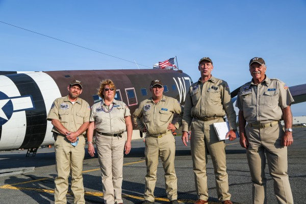 Mike Lindsay (from left), Naomi Wadsworth, Craig Wadsworth, Chris Polhemus and John Lindsay stand on the tarmac on Friday at the Presque Isle airport. They are taking the Whiskey 7, a World War II plane, to Normandy, France, for the 70th anniversary of D-Day.