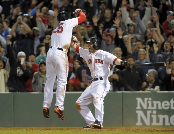 Boston Red Sox second baseman Dustin Pedroia (right) reacts as Jackie Bradley Jr. (25) scores the winning run during the ninth inning of Thursday night's game against the Atlanta Braves at Fenway Park in Boston. The Red Sox won 4-3.