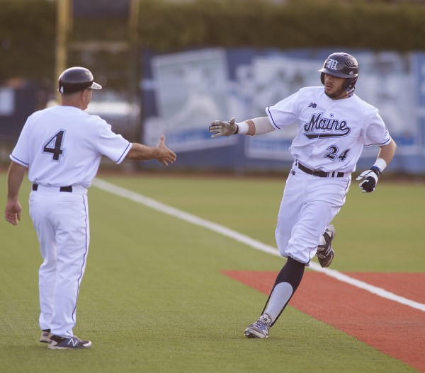 UMaine baseball player Luke Morrill (24) gets a handshake from coach Steve Trimper (left) as he rounds third base on a home run in a game against UMBC at Mahaney Diamond in Orono on Friday.