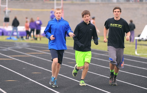 Connor Archer (left) warms up with teammates Jacob Hall (center) and Nick Cowan before the 1,600-meter run during a track and field meet in Hampden Friday.