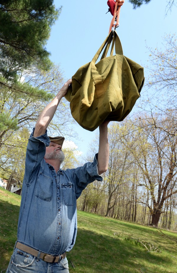 Marc Payne of Avian Haven bird rehabilitation in Freedom grabs the bag holding two baby bald eagles as they are lowered out of the tree by Brent Bibles, Unity College, who climbed the tree to rescue them.