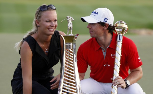 Rory McIlroy of Northern Ireland smiles at his girlfriend tennis player Caroline Wozniacki of Denmark as he poses with his trophy after the fourth and final round of the DP World Tour Championship at Jumeirah Golf Estates in Dubai Nov. 25, 2012.