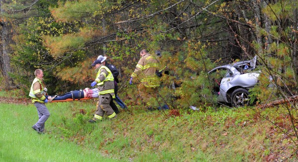 State police troopers and first responders take a person to a waiting ambulance after a car slid off the northbound lane of I-95 in Hampden Monday.  The vehicle appeared to have spun around and hit a group of trees with its rear end. At least one person was injured in the accident.