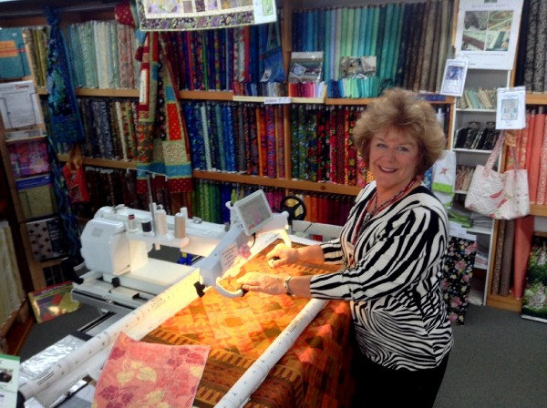 Kala Murphy, owner of The Fabric Garden in Madison, demonstrating a longarm quilting machine.