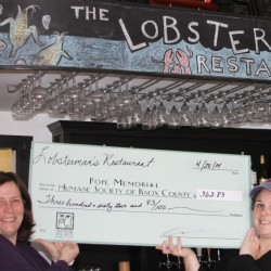 PMHSKC Executive Director Tracy Sala (left) accepts a $362.83 donation check from Christy Adams, co-owner of Lobsterman's Restaurant.