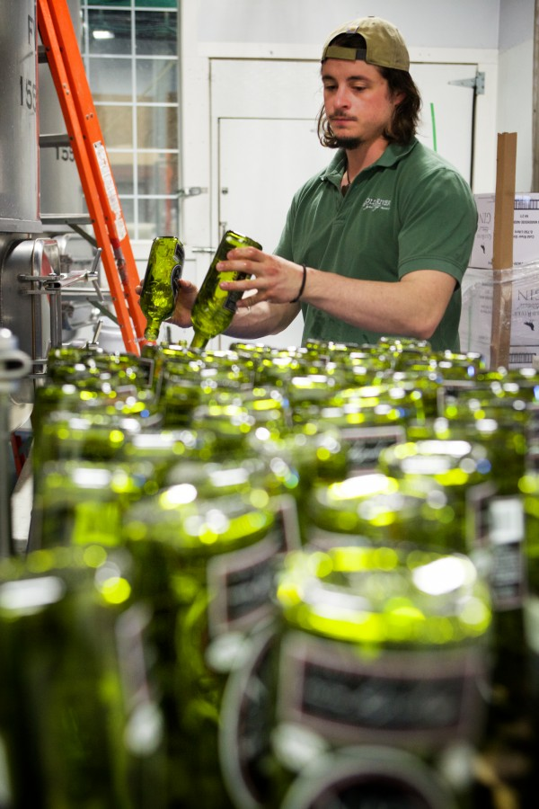 Ian MacLeod washes bottles prior to filling them with Cold River gin at Maine Distilleries on Route 1 in Freeport recently. The company, which launched Cold River vodka in 2005, was the first new Maine distillery in decades.
