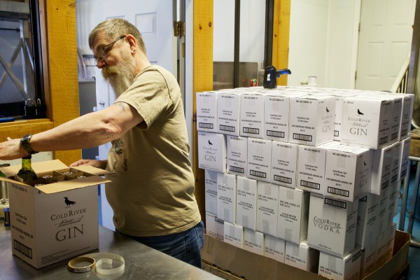 Dan Piotti fills a box with Cold River Gin at Maine Distilleries in Freeport recently. Both the gin and Cold River Vodka are made from Maine potatoes.