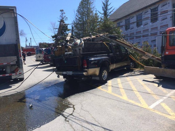 A power pole rests on top of a pickup truck in a municipal parking lot in downtown Bar Harbor Wednesday after a delivery truck snagged an overhead line and pulled the pole over. A police dispatcher said the pole struck multiple parked vehicles and spilled oil from a transformer but that no one was hurt.