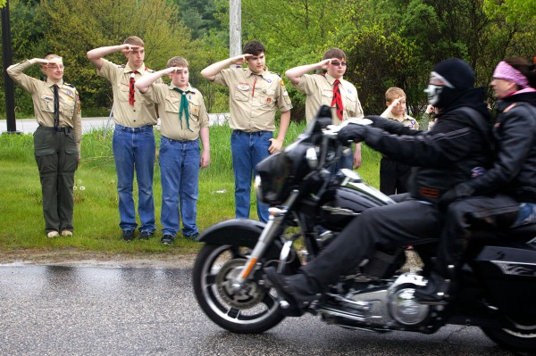 Local Scouts salute Patriot Guard Riders as they rumble out of the Elks Lodge parking lot on outer Congress Street in Portland on Friday morning in the drizzling rain. Each motorcycle carried a memorial stone, in honor of a fallen Maine service member, bound for Mount Katahdin.