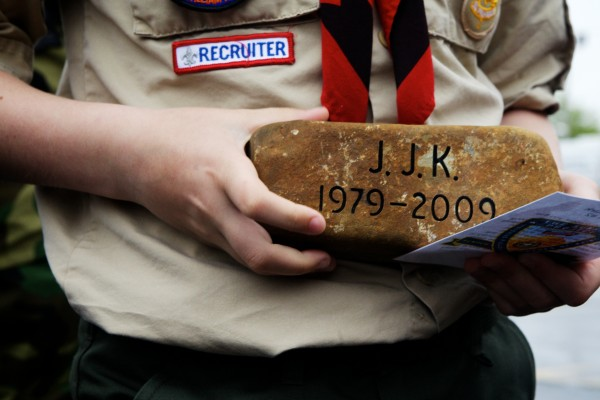Cooper Perry, a Boy Scout from Westbrook, holds a Summit Project stone in memory of U.S. Army Sgt. Joshua Kirk of South Portland, who was killed Oct. 3, 2009 in Kamdesh, Afghanistan. The stones were distributed Friday morning in Portland to motorcyclists transporting them to Mount Katahdin.