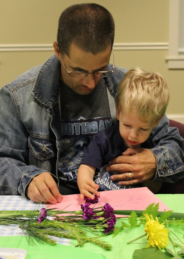A father helps his son create a print using leaves and flowers dipped into washable paint.