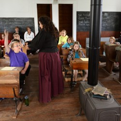 Robbie Giles raises his hand to answer a question from Miss Patty, who was portraying a 19th century schoolteacher.  Third-graders from Bangor Christian School took a field trip to the one-room schoolhouse at the Page Farm & Home Museum on Tuesday.