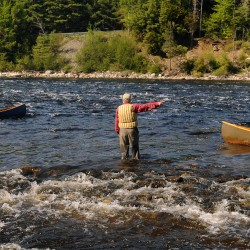 Kevin Slater (center), a Master Maine Guide, directs paddlers around a gravel bar in the rips below the Mattaseunk Dam on Penobscot River Thursday.  Slater was the lead guide of the Thoreau-Wabanaki 150th Anniversary Tour that started on Moosehead Lake in Greenville and is following the route Henry David Thoreau took with his guide Joe Polis in 1857.