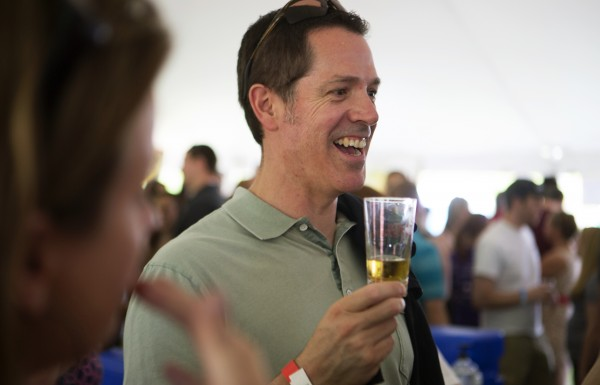 Kevin Forrest laughs with friends while enjoying beer during Bangor's second Tap into Summer Beer Festival on the waterfront in Bangor.