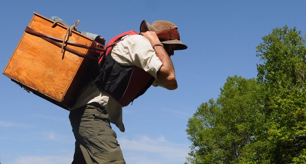 Mike Wilson carries a wannigan containing supplies while portaging around the Mattaseunk Dam on Penobscot River Thursday on the 13th day of the Thoreau-Wabanaki 150th Anniversary Tour.