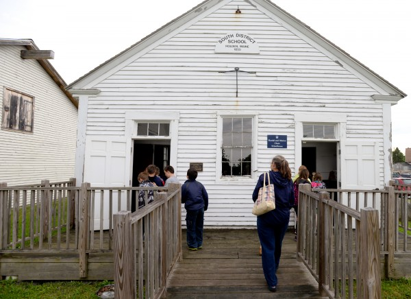 Students enter the one-room schoolhouse at the start of their field trip to the Page Farm & Home Museum on Tuesday.