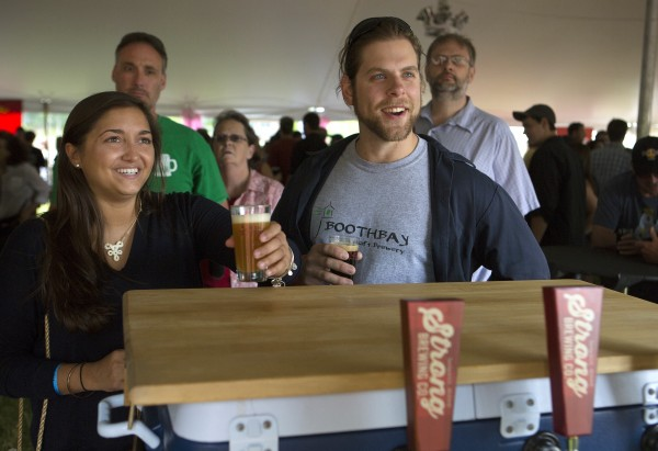 Harley Stevens (left) and Mike Bartles have their glasses filled with Strong Brewing Company beer during Bangor's second Tap into Summer Beer Festival on the waterfront in Bangor.