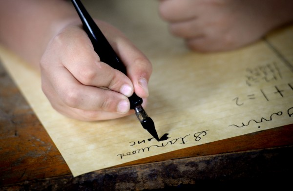Gavin Stanwood, a third-grader at Bangor Christian School, begins a writing assignment with pen and ink at  the Page Farm & Home Museum on Tuesday.