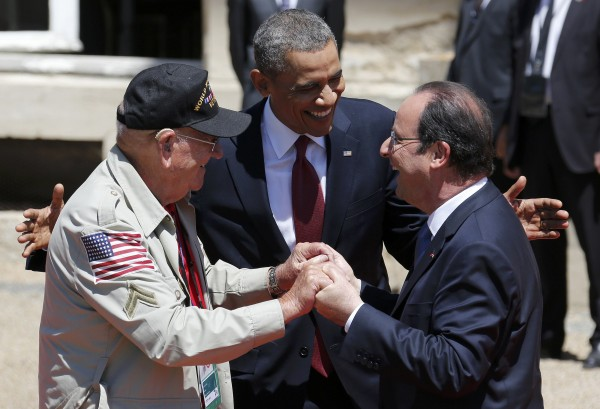 President Barack Obama (center) and French President Francois Hollande (right) smile next to World War II veteran Kenneth &quotRock&quot Merritt as they arrive for the official lunch at Benouville Castle on June 6.