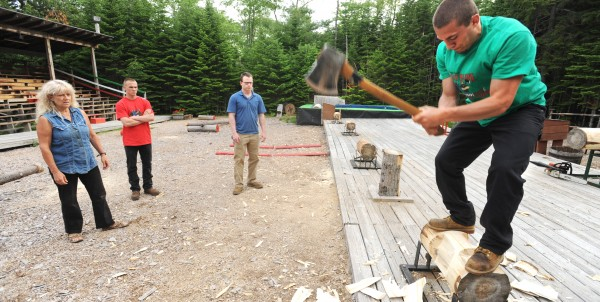Sam Smith practices underhand chop in preparation for the season opening at The Great Maine Lumberjack Show in Trenton as (from left) owner &quotTimber&quot Tina Scheer, Jack Weeks and Justin James look on. The training starts a few weeks before the opening as many of the show participants have little or no experience. She has to teach them the techiques used in the show, which mostly consist of old-fashioned lumberjack work turned into a friendly competition.