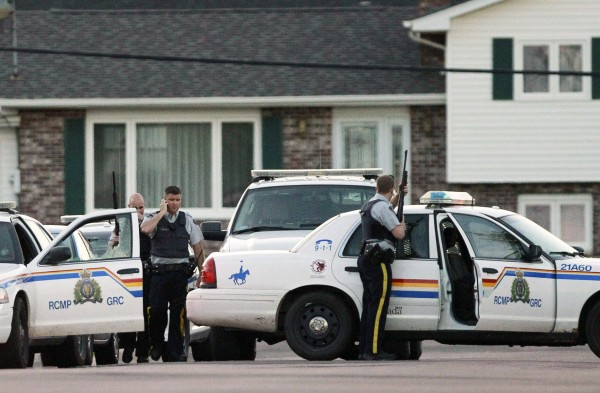 Codiac RCMP officers take cover behind their vehicle in Moncton, New Brunswick June 4, 2014. Three police officers were shot dead and two more were wounded, police said as they conducted a manhunt for a man carrying a rifle and wearing camouflage clothes. Police said they were searching for Justin Bourque, 24, of Moncton.