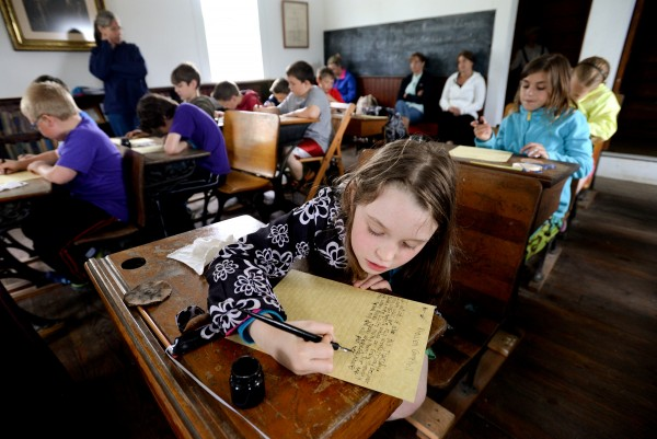 Rhowen Campbell writes an essay about summer with pen and ink on parchment paper at the Page Farm & Home Museum on Tuesday. She and her third-grade class were on a field trip to learn about being a student in 1867.