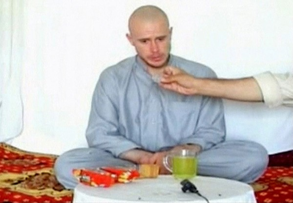 U.S. Army Private Bowe Bergdahl watches as one of his captors display his identity tag to the camera at an unknown location in Afghanistan in this July 19, 2009 file still image taken from video. Bergdahl, held for nearly five years by the Taliban after being captured in Afghanistan, has been released and is now in U.S. custody after years of on and off negotiations.