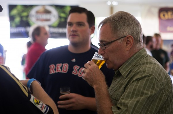 Rick Kimball (right) enjoys a beer during Bangor's second Tap into Summer Beer Festival on the waterfront in Bangor.