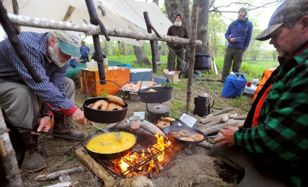 Maine Guides Kevin Slater (left) and Glen Horne (right) prepare breakfast for members of the expedition on Brown Island Friday.