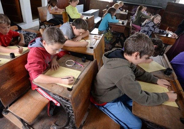 Third-graders Ryan Libby (from left), Brady Campbell and Micah Robert use pen and ink to write an essay about summer at the Page Farm & Home Museum on Tuesday.