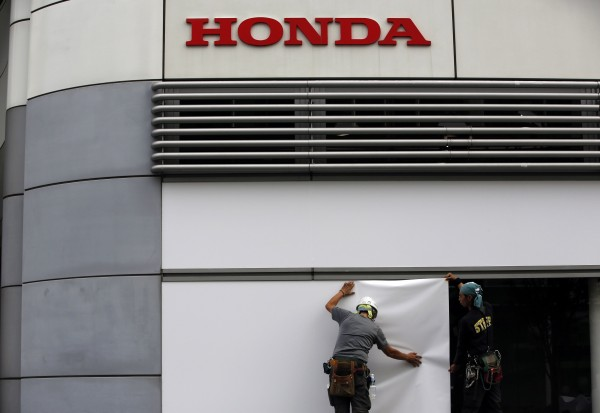 Workers stand under the logo of Honda Motor Co. outside the company's headquarters in Tokyo, in this file picture taken October 30, 2013.