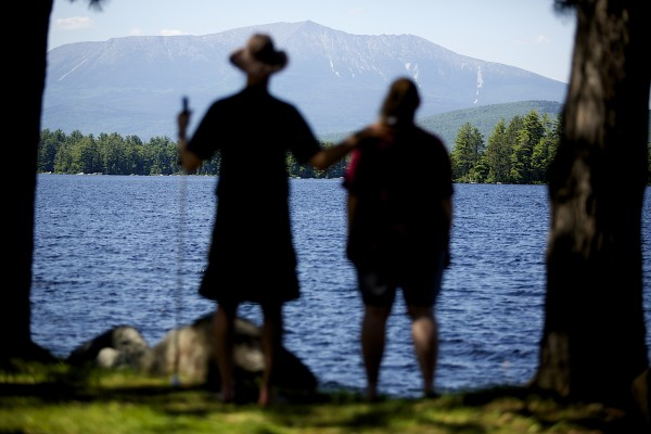 Roger Poulin (left), a deaf and blind man from Washington, and his service provider Roni Lepore, who also is deaf, look out at Millinocket Lake on Friday.