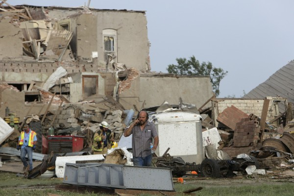 A man talks on the phone in front of tornado-damaged buildings in Pilger, Nebraska June 16, 2014. A swarm of tornadoes, some appearing two at a time, struck several farming communities in northeastern Nebraska on Monday, killing at least one person and injuring 16 in the tiny town of Pilger.
