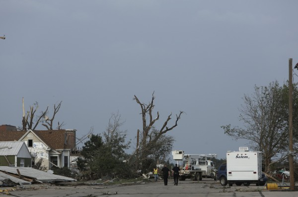 Law enforcement officials walk down the evacuated streets of Pilger, Nebraska June 16, 2014. A swarm of tornadoes, some appearing two at a time, struck several farming communities in northeastern Nebraska on Monday, killing at least one person and injuring 16 in one tiny town obliterated by a direct hit, officials said.