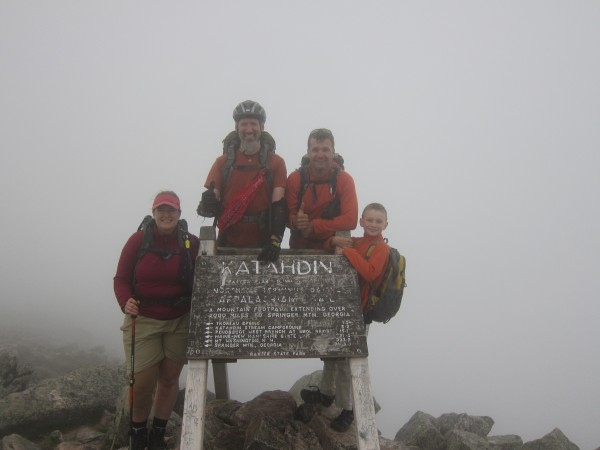 Roni Lepore (from left) and Roger Poulin, 46, of Washington state summit Mount Katahdin on June 24 to complete the Appalachian Trail, with support team registered Maine guide David Whitney and his son Ateon. Poulin is deaf and blind and hiked the entire trail over four years with his support service provider Roni Lepore, who is deaf.